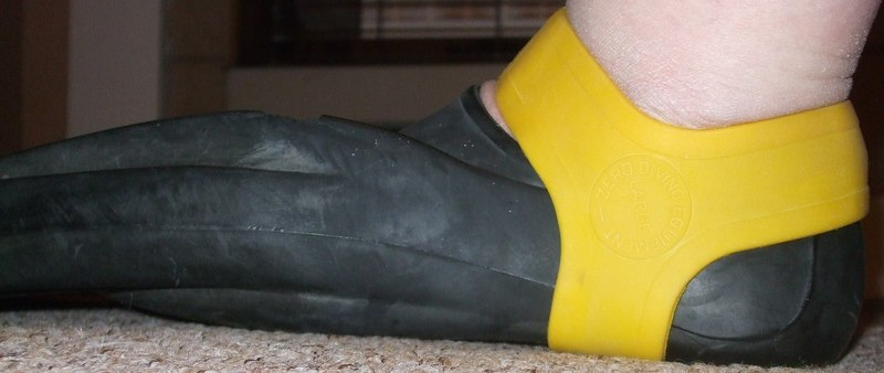 1920px-Yellow_fin_grip_retaining_a_Technisub_Ala_swimming_fin_on_the_foot.jpg