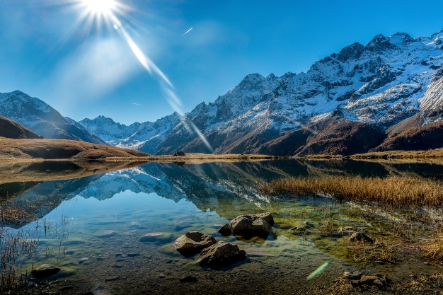 beautiful-shot-crystal-clear-lake-snowy-mountain-base-during-sunny-day_181624-5459.jpg