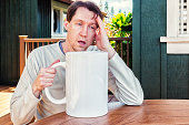 man-with-extra-large-coffee-and-headache-picture-id172311886?s=170x170.jpg